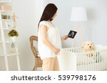 Young Pregnant Woman Holding...