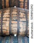 Small photo of Pile 0f old oak barrels in cellar with bung. Side view.