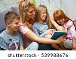 mother reading a book to her... | Shutterstock . vector #539988676