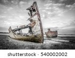 Small photo of Destroyed decaying old boats rusting and corroding on the bank of a river near an estuary.