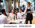 Stock photo portrait of smiling adult friends in outdoors restaurant and smiling waitress focus on blonde girl 540638545