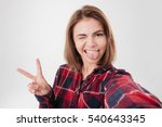 Stock photo funny cute girl winking and showing tongue while taking selfie isolated on a white background 540643345