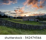 A Stone Barn At Sunset In The...