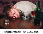 Drunk man sleep on wooden table.