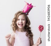 Small photo of Beautiful little candy princess girl in crown holding big pink heart lollipop and smiling