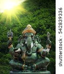 Small photo of Green ganesh statue in temple thailand with selective focus and blurry background with sun lighting flare effect.