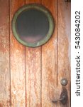 Small photo of Old wooden door with a porthole on the abandoned ship