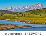 Grand Teton mountain range, partly covered in snow, with green forest, field, and small river in the foreground. It was taken on a sunny day in summer at the gateway to Grand Teton national park.