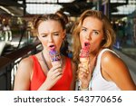 Small photo of Fashion portrait of two young beautiful women friends in shopping mall with colored ice cream cone. Smiling and going shopping. Wearing stylish t-shirts, fashion accessories. Showing singers. Close up