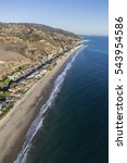 Small photo of Aerial of large affluent beach homes along the sandy Pacific coast in Malibu California.