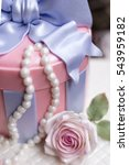 Small photo of butter cake decorated in sweet round gift box with pastel pink rose fondant and white pearl (selective focus on rose fondant only)
