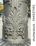 Small photo of Detail of decoration carved on iron street lamps in Barcelona city, Spain. This ornament represents the classic acanthus plant, usually used by ancient Greek culture, Rome and neoclassic style.
