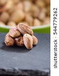 Small photo of Small pile of shelled roasted pistachio nuts with bowl of unshelled ones in background. All set on slate serving plates