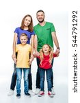 Small photo of Family standing in colorful t-shirts and smiling at camera isolated on white