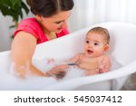 Small photo of Mother and child bathing together playfully at home.