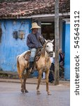 Small photo of VINALES, CUBA - JANUARY 21, 2016: Peasant with horse walks the streets of the village under the incipient rain