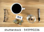 Small photo of ISA words on desk with coins and pen