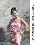 Small photo of Expectant mother on seashore. Pregnant woman in sarong standing in water arms akimbo looking at camera