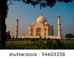 A tree provides a frame around the Taj Mahal at sunset. - stock photo