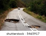 A Badly Damaged Road With Sink...