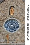 Small photo of ILE D`ORLEANS, CANADA - SEPTEMBER 16, 2016: The golden statue of a saint looks out from a high alcove above a round window in the historic Saint-Francois Ile d'Orleans church, built in 1734.