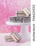 Small photo of Traditional Australian Lamington Cakes ion cake stand against a pink and white background, with applied faded retro style filters.