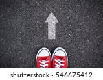 red sneakers with arrow on road ... | Shutterstock . vector #546675412