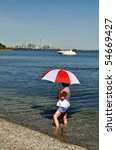 Woman with red and white umbrella looking at Toronto skyline - stock photo