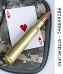 Small photo of Ace of hearts and fifty caliber bullet.