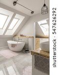 Small photo of Oval freestanding bath in modern spacious white marble bathroom with attic windows
