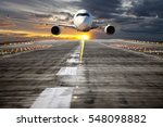 Small photo of A passenger plane takes off from the airport runway. Aircraft flies low over the airfield at sunset sky background. Airplane front view.