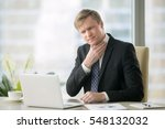 Stock photo young businessman working with laptop at desk in the office hand at his neck feeling unwell have 548132032