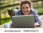 Stock photo woman working with her laptop outdoors or having fun with it 548245672