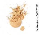 Small photo of Smashed and cracked golden eye shadow isolated on a white background.