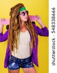Small photo of Pretty girl with dreadlocks and green do-rag holding pink skateboard and smiling