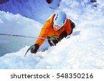 man climbing frozen waterfall. | Shutterstock . vector #548350216