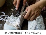Small photo of boy washes a pair of dirty white shoes , sneakers by hands with brush /cleaning shoes at home