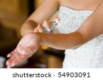 A horizontal photo in natural light of a caucasian woman spraying perfume on her wrist on her wedding day. - stock photo