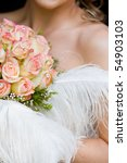 A vertical close up of a caucasian bride with a bouquet of yellow and pink roses - stock photo