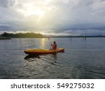 A Female Kayaker Paddles Acros...
