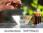 hand pouring essential oil in a ... | Shutterstock . vector #549750622