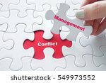 Small photo of Close up of girl's hand placing the last jigsaw puzzle piece with word Conflict Management