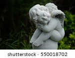 A White Sculpture Cupid In The...