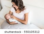young mother with baby in bed | Shutterstock . vector #550105312
