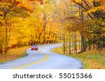 An autumn road with a motion-blurred car on the curve - stock photo