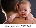 Infant looking over his fathers shoulder - stock photo