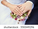 Small photo of Hands of bride and groom with rings on wedding bouquet. Marriage concept.