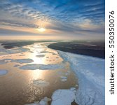 Small photo of Aerial view great river with spring debacle during sundown. Floating of ice.