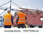 rear view of workers talking... | Shutterstock . vector #550704616