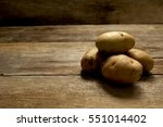 Potatoes On Wooden Background.